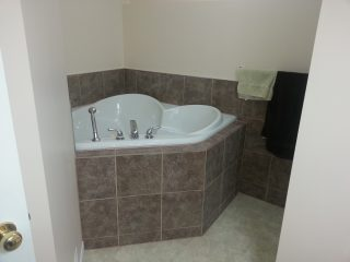 Residential bathroom renovation with two-person soaker tub.