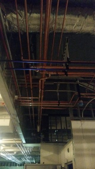 Commercial ceiling void runs for potable water, heating, and sewer.